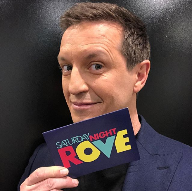 Rove McManus holding a cue card backstage on the TV set for Saturday Night Rove