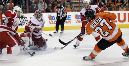 Philadelphia Flyers center Maxime Talbot (27) scores a goal as the puck goes between Detroit Red Wings defenseman Niklas Kronwall (55), from Sweden, and goalie Joey MacDonald (31) in the second period of an NHL hockey game Tuesday, March 6, 2012, in Philadelphia. (AP Photo/Alex Brandon)