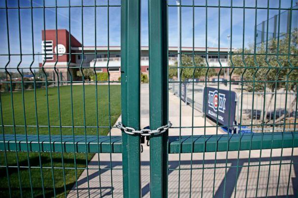 PHOTO: A gate at the Chicago Cubs practice facility at Sloan Park in Mesa, Ariz., is closed and locked, March 16, 2020. The remainder of spring training baseball games have been canceled due to the coronavirus. (Sue Ogrocki/AP)