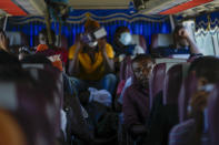 Migrants, many from from Haiti, sit on a bus as they wait to be transported to another shelter on their journey through Panama, trying to reach the United States, in Lajas Blancas, Darien province, Panama, Friday, Oct. 1, 2021. (AP Photo/Arnulfo Franco)
