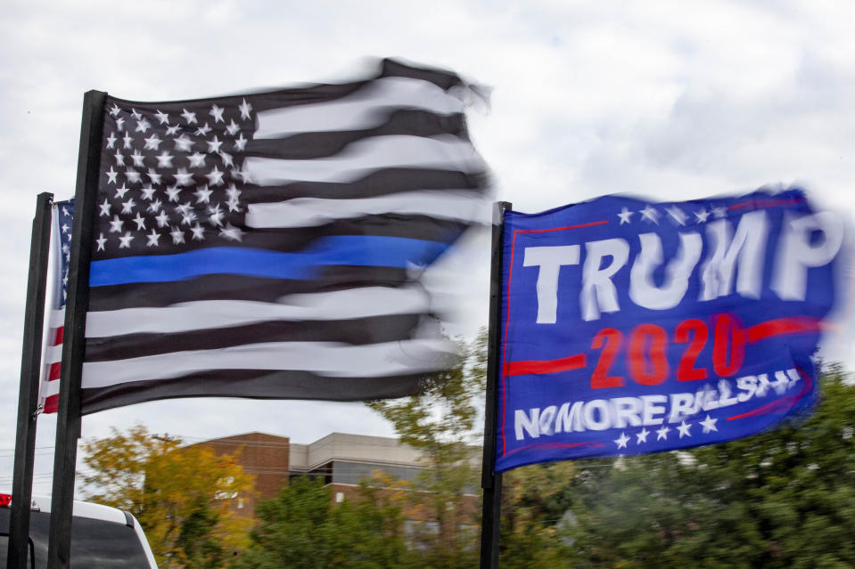 "An American flag, a ""Back the Blue"" flag and a Trump 2020 flag are flown from the back of a truck that is part of the Trump Parade on I-270. (Photo by Stephen Zenner/SOPA Images/LightRocket via Getty Images)"