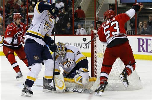 Carolina Hurricanes' Eric Staal (12) shoots and scores on Nashville Predators goalie Anders Lindback, of Sweden, as Hurricanes' Jeff Skinner (53) assists and Predtors Roman Josi, of the Czech Republic, defends during the second period of an NHL hockey game in Raleigh, N.C., Tuesday, Feb. 28, 2012. (AP Photo/Gerry Broome)