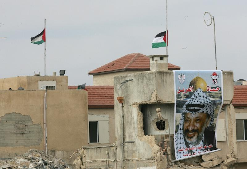 Flags fly at half-mast over the destroyed Muqataa compound after the death of Palestinian leader Yasser Arafat, November 11, 2004 at his West Bank headquarters, in Ramallah (AFP Photo/Thomas Coex)