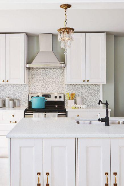 <p>A neutral circle pattern, brass accents, and an ornate pendant add to this kitchen's high-end look. </p>