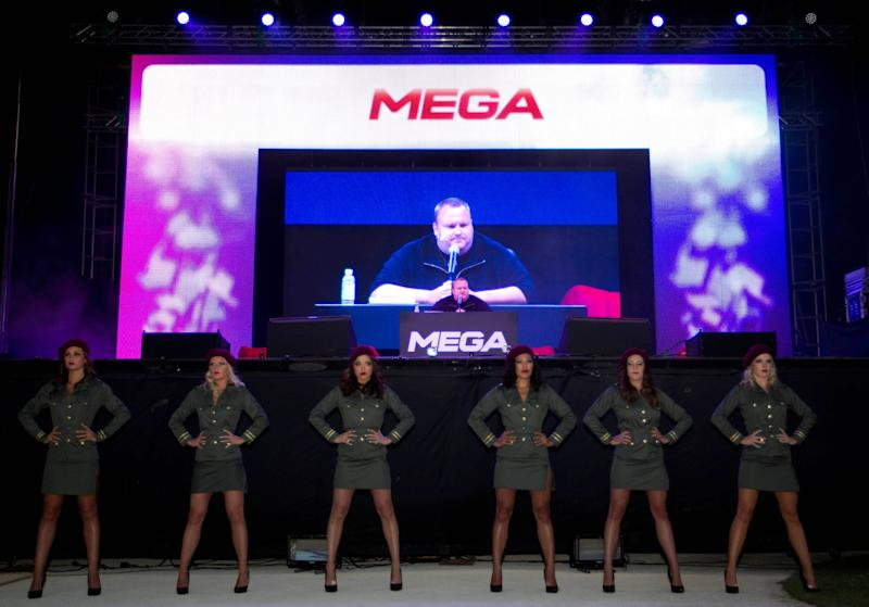"""Indicted Megaupload founder Kim Dotcom appears on a large screen during the launch of a new file-sharing website called """"Mega"""" at his Coatesville mansion in Auckland, New Zealand, Sunday, Jan. 20, 2013. The colorful entrepreneur unveiled the site ahead of a lavish gala and press conference on the anniversary of his arrest on racketeering charges related to his now-shuttered Megaupload file-sharing site. (AP Photo/New Zealand Herald, Richard Robinson) New Zealand Out, Australia Out"""