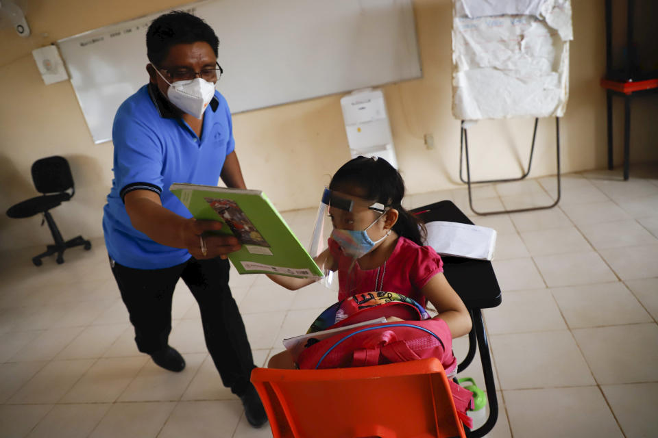 Wering a mask to curb the spread of the new coronavirus, a teacher hands a workbook to his 10-year-old student Jade Chan Puc during the first day of class at the Valentin Gomez Farias Indigenous Primary School in Montebello, Hecelchakan, Campeche state, Monday, April 19, 2021. Campeche is the first state to transition back to the classroom after a year of remote learning due to the pandemic. (AP Photo/Martin Zetina)