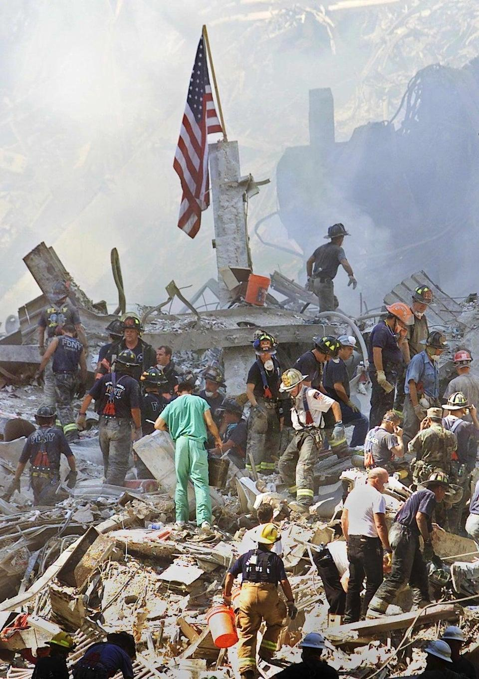 An American flag is posted in the rubble of the World Trade Centre as firemen and rescue workers clear the debris (EPA)