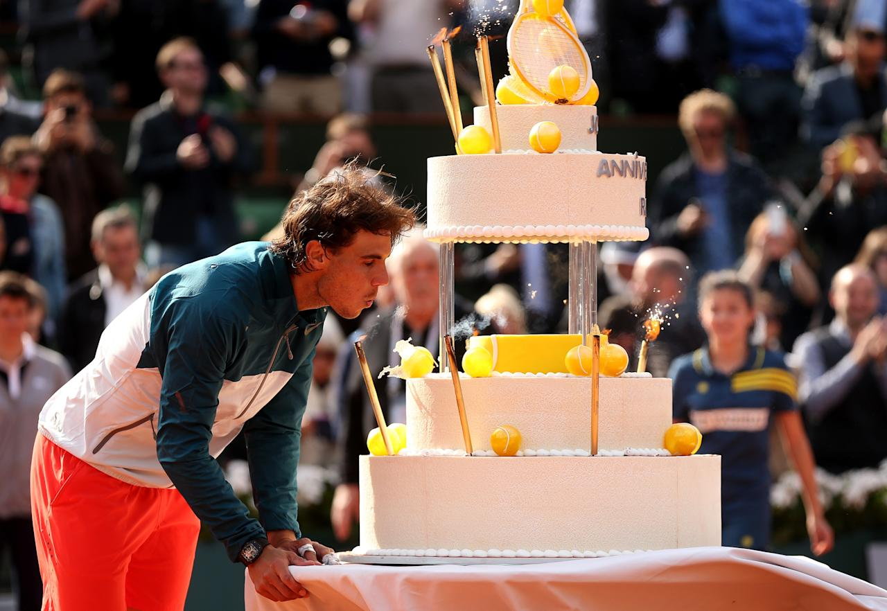 PARIS, FRANCE - JUNE 03:  Rafael Nadal of Spain  blows out the candles on a giant birthday cake after victory in his Men's Singles match against Kei Nishikori of Japan during day nine of the French Open at Roland Garros on June 3, 2013 in Paris, France.  (Photo by Matthew Stockman/Getty Images)