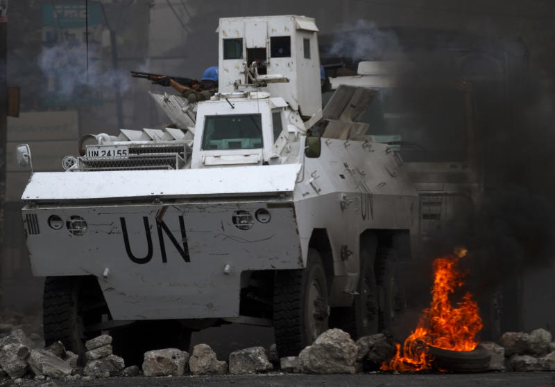 U.N. peacekeepers shoot rubber bullets to protesters as they ride through a barricade in Port-au-Prince, Haiti, Friday, Dec. 10, 2010. Despite the country's electoral council announcement Thursday of a compromise to recount votes, clashes between protesters and authorities continued in port-au-Prince. (AP Photo/Guillermo Arias)