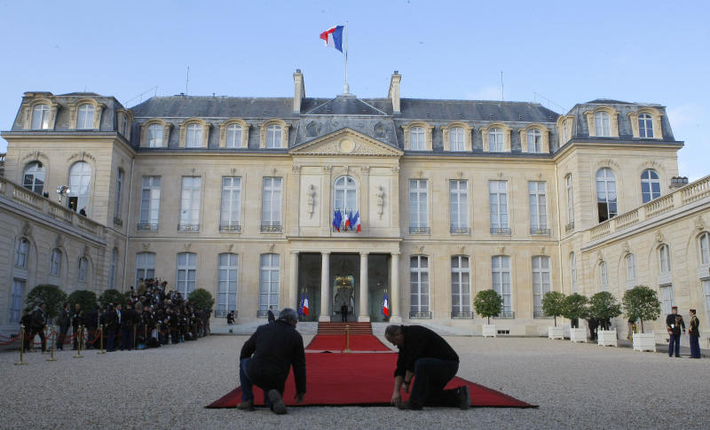 Workers prepare the red carpet for the takeover ceremony between outgoing President Nicolas Sarkozy and President-elect Francois Hollande, Tuesday, May 15, 2012, at the Elysee Palace in Paris. (AP Photo/Jacques Brinon)