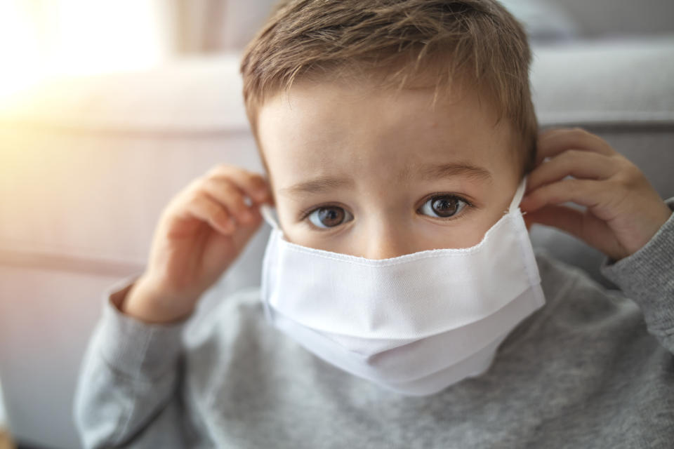 2-3 years old cute child wearing surgical mask. Little boy trying to stay healthy by wearing a mask to protect him against corona virus covid-19 / 2019-nCov. Little boy wearing anti virus mask staying at home