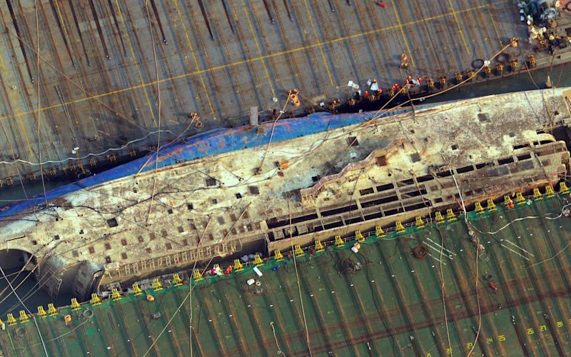 This aerial image shows part of the damaged Sewol ferry between two barges after being raised during a salvage operation at sea off the southwestern island of Jindo - Credit: AFP
