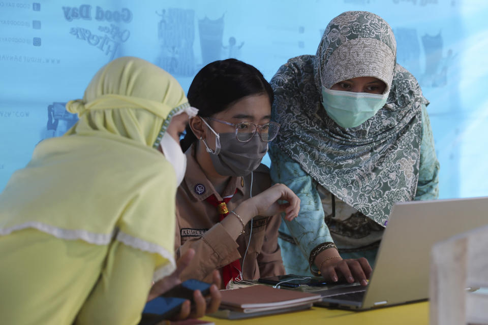 A mother, right, and her daughter, center, wear face masks to help curb the spread of the new coronavirus as they use free wifi to access an online lesson inside a temporary tent in Jakarta, Indonesia, Wednesday, Aug. 12, 2020. In some areas of the country, students are still yet to go to school due to the coronavirus. (AP Photo/Achmad Ibrahim)