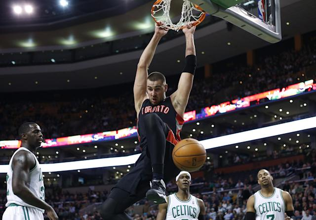 Toronto Raptors center Jonas Valanciunas (17) dunks in front of Boston Celtics forward Brandon Bass, left, guard Rajon Rondo, middle, and center Jared Sullinger (7) in the first quarter of an NBA basketball game in Boston, Wednesday, March 26, 2014. (AP Photo/Elise Amendola)