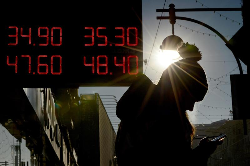 A woman stands under a board listing foreign currency rates against the Russian ruble just outside an exchange office in central Moscow, on January 31, 2014