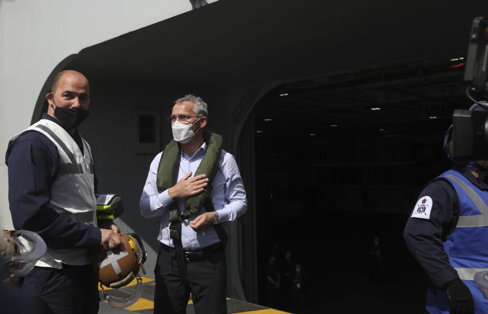 NATO Secretary General Jens Stoltenberg, center, arrives on board the aircraft carrier HMS Queen Elizabeth as it participates in the NATO Steadfast Defender 2021 exercise off the coast of Portugal, Thursday, May 27, 2021. NATO has helped provide security in Afghanistan for almost two decades but the government and armed forces in the conflict-torn country are strong enough to stand on their own feet without international troops to back them, the head of the military organization said Thursday. (AP Photo/Ana Brigida)