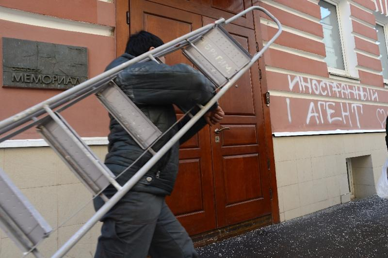 """A man carrying a stepladder as he walks past one of the entrances to the Memorial rights group office in Moscow on March 21, 2013, alongside graffiti reading: """"A Foreign Agent"""" (AFP Photo/Kirill Kudryavtsev)"""