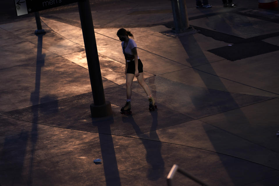 A woman roller skates along the Strip in Las Vegas, Feb. 10, 2021. The toll of the coronavirus is reshaping Las Vegas almost a year after the pandemic took hold. The tourist destination known for bright lights, big crowds, indulgent meals and headline shows is a much quieter place these days. (AP Photo/John Locher)