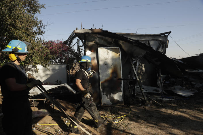 Israeli firefighters arrive at kibbutz in south Israel hit by rocket fire from Gaza that killed two Thai workers inside a packaging plant in southern Israel , Tuesday, May 18, 2021. Since the fighting began last week, the Israeli military has launched hundreds of airstrikes it says are targeting Hamas' militant infrastructure, while Palestinian militants have fired thousands of rockets into Israel. (AP Photo/Maya Alleruzzo)