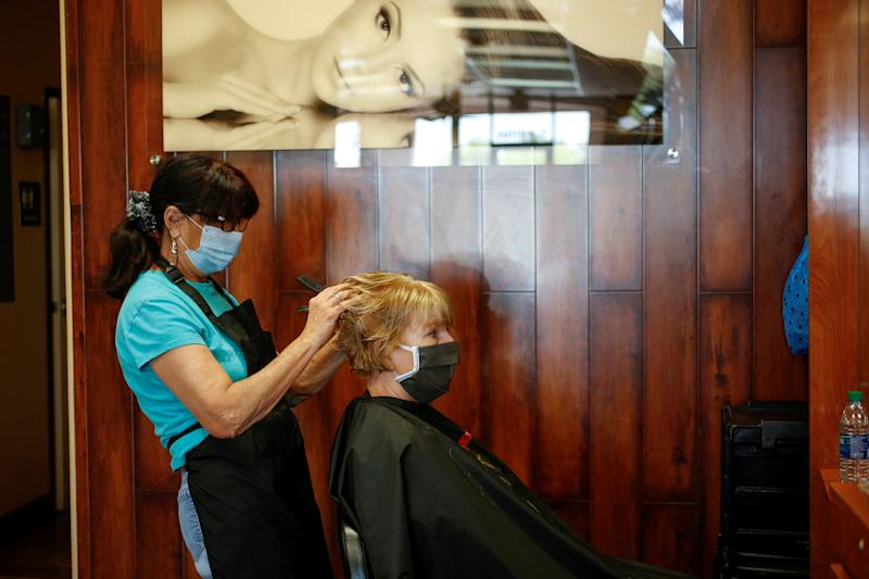 Image: Donna Ferraro cuts and styles Jan Campbell?s hair at Passions Salon during the phased reopening from the coronavirus disease (COVID-19) restrictions, in Cave Creek (Nicole Neri / Reuters file)