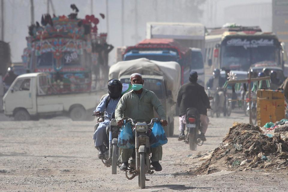 A man wears a face mask as he rides a motorcycle amid the ongoing COVID-19 pandemic in Pakistan (EPA)