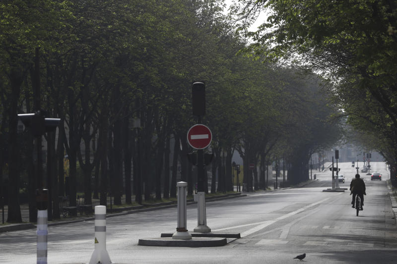 A man rides a bicycle in an empty street of Paris, Friday, March 20, 2020. French President Emmanuel Macron said that for 15 days starting at noon on Tuesday, people will be allowed to leave the place they live only for necessary activities such as shopping for food, going to work or taking a walk. For most people, the new coronavirus causes only mild or moderate symptoms. For some it can cause more severe illness, especially in older adults and people with existing health problems. (AP Photo/Thibault Camus)