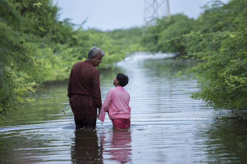 Abdul Jabbar and his son Muhammad Hashim walk across floodwater. Their home was devastated during the monsoon floodsSaiyna Bashir/Arete/WFP