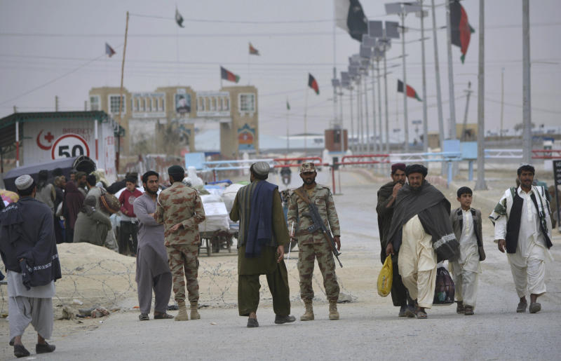 Pakistani paramilitary soldiers stand guard while people wait for opening border crossing, in Chaman, Pakistan, Monday, March 20, 2017. Pakistan's prime minister ordered the reopening of the country's border with Afghanistan on Monday, ending a protracted closure that has cost businesses on both sides millions of dollars and deepened tensions between the two neighbors. (AP Photo/Matiullah Achakzai)