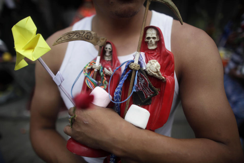 FILE - In this Oct. 1, 2009 file photo, a man carries two statues of the folk saint Santa Muerte, or Death Saint in Mexico City. Mexican prosecutors are investigating a family outside a small town near the U.S. border as alleged members of a cult who sacrificed three people to the Saint Death, a figure adored mostly by outlaws but whose popularity is growing across Mexico and among Hispanics in the United States. The first of the three victims was apparently killed in 2009, the second in 2010 and the latest in March 2012. (Photo/Dario Lopez-Mills, File)
