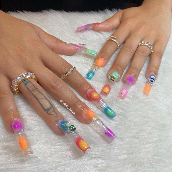 Clear manicures are a perfect base for colorful nail designs, and this orb manicure by Vo is evidence. They used an airbrushing technique to spread the orange, blue, yellow, purple, and pink hues in this set. To complete the manicure, they added a few colorful gems and 3D water droplets.