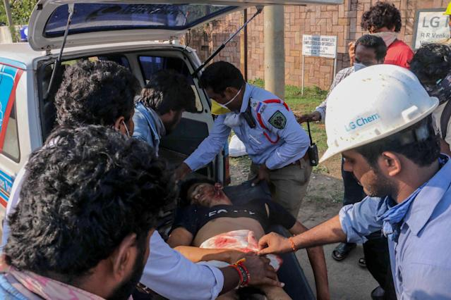 Police personnel and people carry a man (C) that has fainted following a gas leak incident to transport him to a hospital in Visakhapatnam on May 7, 2020. - At least seven people were killed and hundreds hospitalised after a pre-dawn gas leak at a chemical plant in eastern India on May 7 that left unconscious victims lying in the streets, authorities said. The gas escaped out of tanks at a complex owned by South Korea's LG Chem that had suspended operations because of India's coronavirus lockdown. (Photo by STR / AFP) (Photo by STR/AFP via Getty Images)