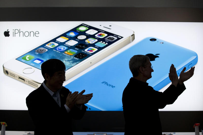FILE - In this Jan. 17, 2014 file photo, Apple CEO Tim Cook, right, and China Mobile's chairman Xi Guohua are silhouetted against a screen showing iPhone products as they applaud during a promotional event that marks the opening day of sales of China Mobile's 4G iPhone 5s and iPhone 5c at a shop of the world's largest mobile phone operator in Beijing, China. The high-stakes battle between the world's largest smartphone makers is scheduled to wrap up this week after a monthlong trial that has pulled the curtain back on just how very cutthroat the competition is between Apple and Samsung. Closing arguments in the patent-infringement case are scheduled to begin Monday, April 28 with the two tech giants accusing each other, once again, of ripping off designs and features. At stake: $2 billion if Samsung loses, a few hundred million if Apple loses. (AP Photo/Alexander F. Yuan, File)