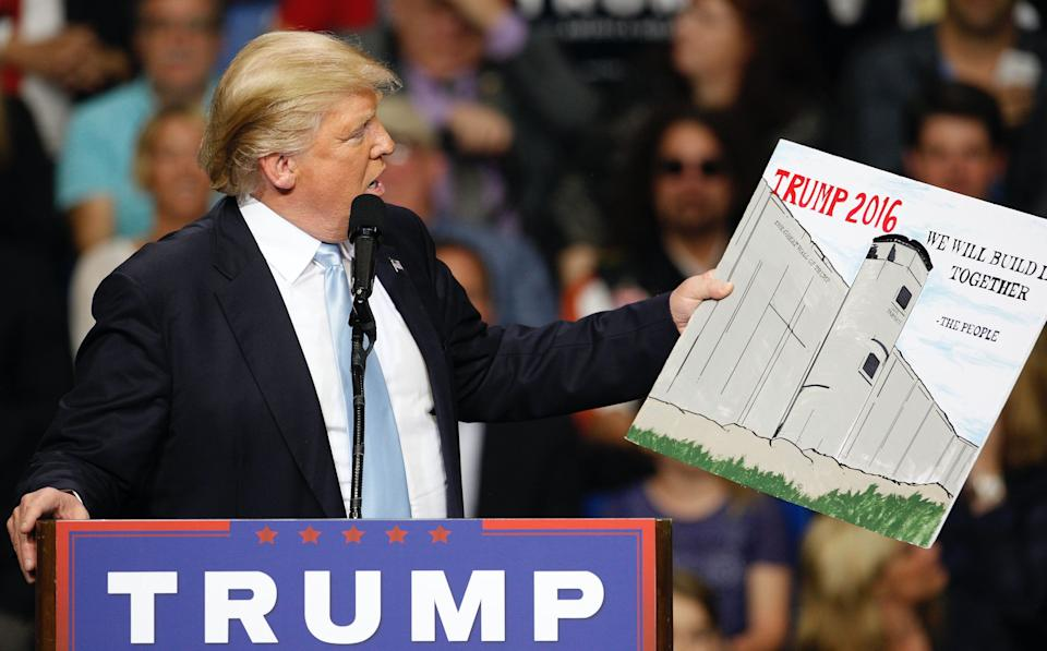 U.S. Republican presidential candidate Donald Trump holds a sign supporting his plan to build a wall between the United States and Mexico that he borrowed from a member of the audience at his campaign rally in Fayetteville, North Carolina March 9, 2016. (Photo: REUTERS/Jonathan Drake)