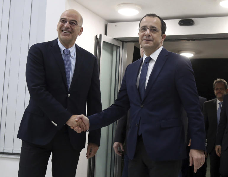 Greece's Foreign Minister Nikos Dendias, left, shake hands with Cypriot counterpart Nikos Christodoulides before their meeting at Cyprus' main airport in the coastal town of Larnaca on Sunday, December 22, 2019. Dendias stopped off in Cyprus following a visit to Libya for contacts with Libyan National Army leader, General Khalifa Haftar and later in Egypt for a meeting with Foreign Minister Sameh Shoukry. Top of the agenda during Dendias' contacts was a maritime border deal that Turkey signed with Libya's U.N.-recognized government that Greece, Cyprus and Egypt have denounced as contrary to international law.(AP Photo/Philippos Christou)