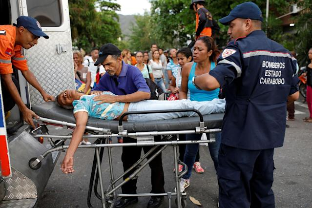 <p>Paramedics help a relative of inmates held at the General Command of the Carabobo Police, who fainted, outside the prison, where a fire occurred in the cells area, according to local media, in Valencia, Venezuela, March 28, 2018. (Photo: Carlos Garcia Rawlins/Reuters) </p>