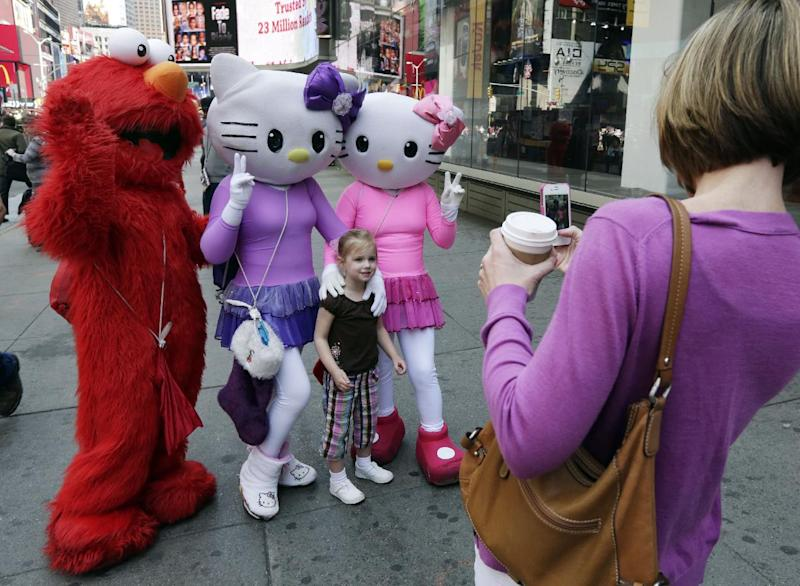 Elmo and two Hello Kitty characters pose for photos with a little girl in New York's Times Square, Tuesday, April 9, 2013. A string of arrests in the last few months has brought unwelcome attention to the growing number of people, mostly poor immigrants, who make a living by donning character outfits, roaming Times Square and charging tourists a few dollars to pose with them in photos. (AP Photo/Richard Drew)