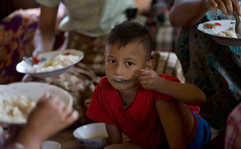 A Muslim boy eats a meal at a Buddhist temple following sectarian violence in Lashio, northern Shan State, Myanmar, Thursday, May 30, 2013. More than 1,000 Muslims who fled Myanmar's latest bout of sectarian violence huddled Thursday in a Buddhist monastery guarded by army soldiers as calm returned to this northeastern city, though burnt out buildings leveled by Buddhist rioters still smoldered. (AP Photo/Gemunu Amarasinghe)