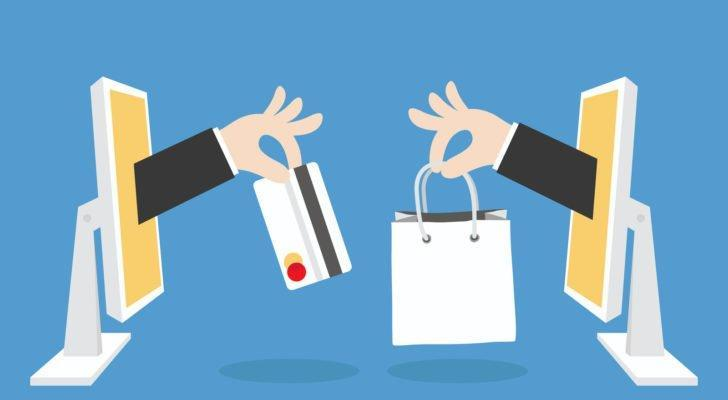 E-commerce concept showing online retail exchange between two computer screens on light blue background.