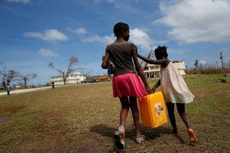 Children carry a plastic container filled with water in a damaged orphanage after Hurricane Matthew passes Jeremie, Haiti, October 11, 2016. REUTERS/Carlos Garcia Rawlins