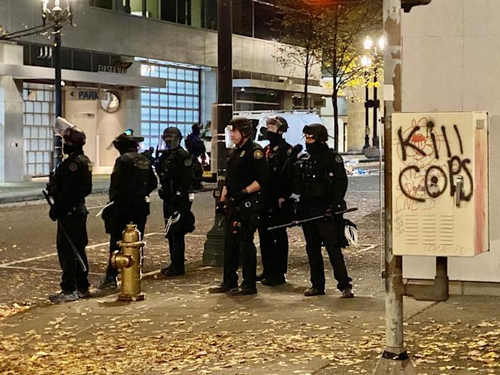 Portland police officers wait for anarchists who set a fire to make their next move.