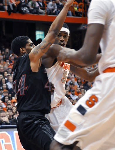 Syracuse's C.J. Fair looks to pass against Cincinnati's Jaquon Parker during the second half of an NCAA college basketball game in Syracuse, N.Y., Monday, Jan. 21, 2013. Syracuse won 57-55. (AP Photo/Kevin Rivoli)