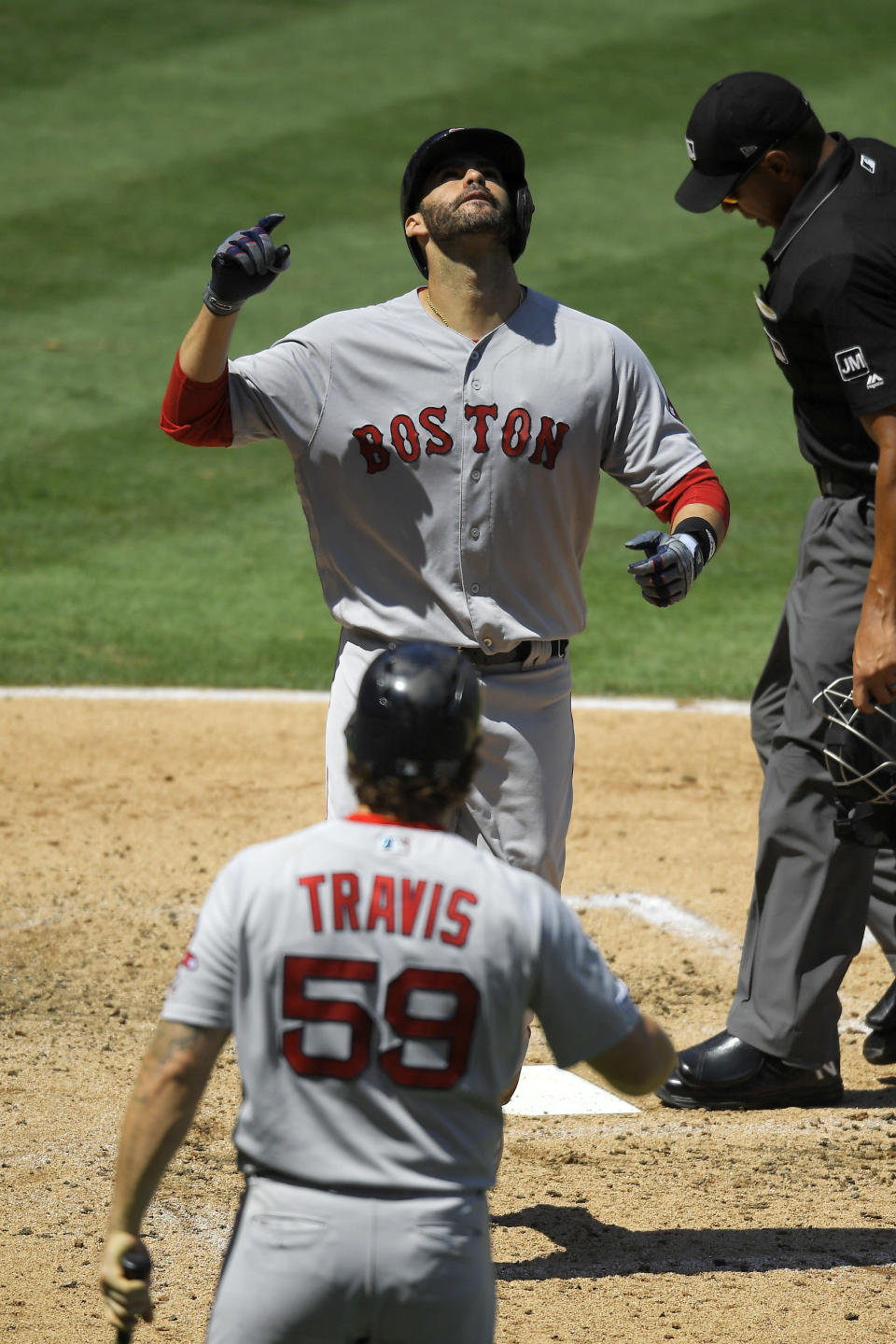Boston Red Sox's J.D. Martinez, top, gestures as he scores on his solo home run as Sam Travis, bottom, waits to congratulate him during the third inning of a baseball game against the Los Angeles Angels, Sunday, Sept. 1, 2019, in Anaheim, Calif. (AP Photo/Mark J. Terrill)