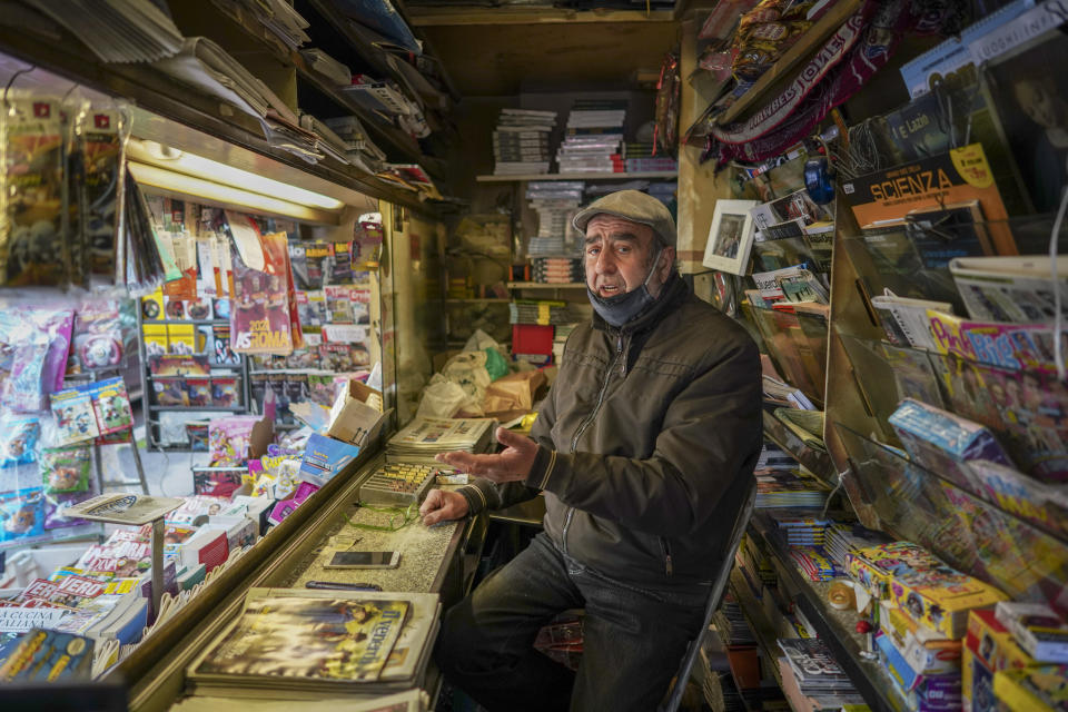 Armando Alviti, 71, sits inside his newspaper kiosk, in Rome, Friday, Dec. 4, 2020. In Italy, which has the world's second-oldest population, many people in their 70s and older have kept working through the COVID-19 pandemic. From neighborhood newsstand dealers to farmers bring crops to market, they are defying stereotypic labels that depict the old as a monolithic category that's fragile and in need of protection. (AP Photo/Andrew Medichini)