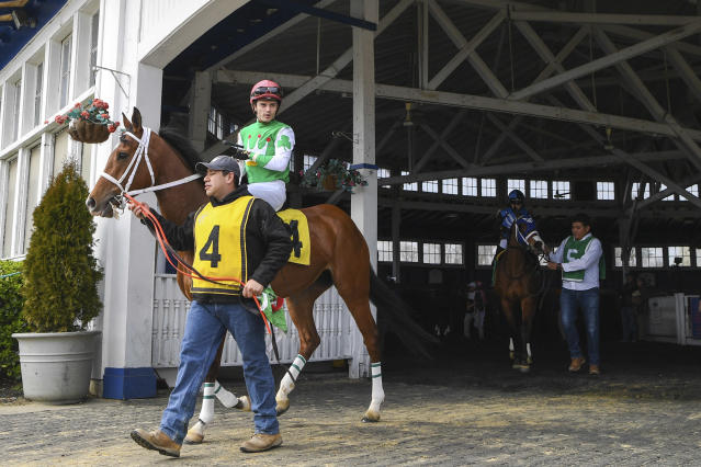 Lady Banba (4) ridden by jockey Sheldon Russell is lead out of the paddock before a horse race at Laurel Park Race Track, an event that allowed no spectators, Saturday, March 14, 2020, in Laurel, Md. While most of the sports world is idled by the coronavirus pandemic, horse racing runs on. (AP Photo/Terrance Williams)