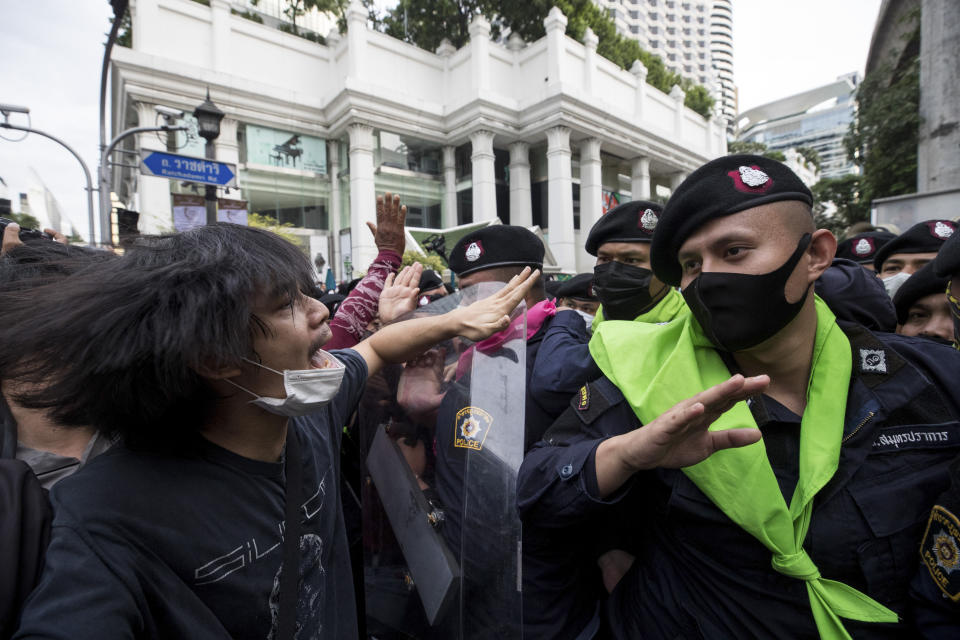 Police official scuffle with pro-democracy protesters during a protest as they occupied the main road in the central business district in Bangkok, Thailand, Thursday, Oct. 15, 2020. Thailand's government declared a strict new state of emergency for the capital on Thursday, a day after a student-led protest against the country's traditional establishment saw an extraordinary moment in which demonstrators heckled a royal motorcade. (AP Photo/Wason Wanichakorn)