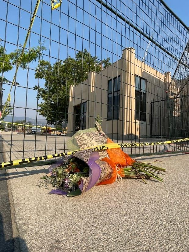 A flower memorial is shown near the site of the July 12 crane collapse in Kelowna, B.C., which killed five people. (Anita Sthankiya/CBC - image credit)