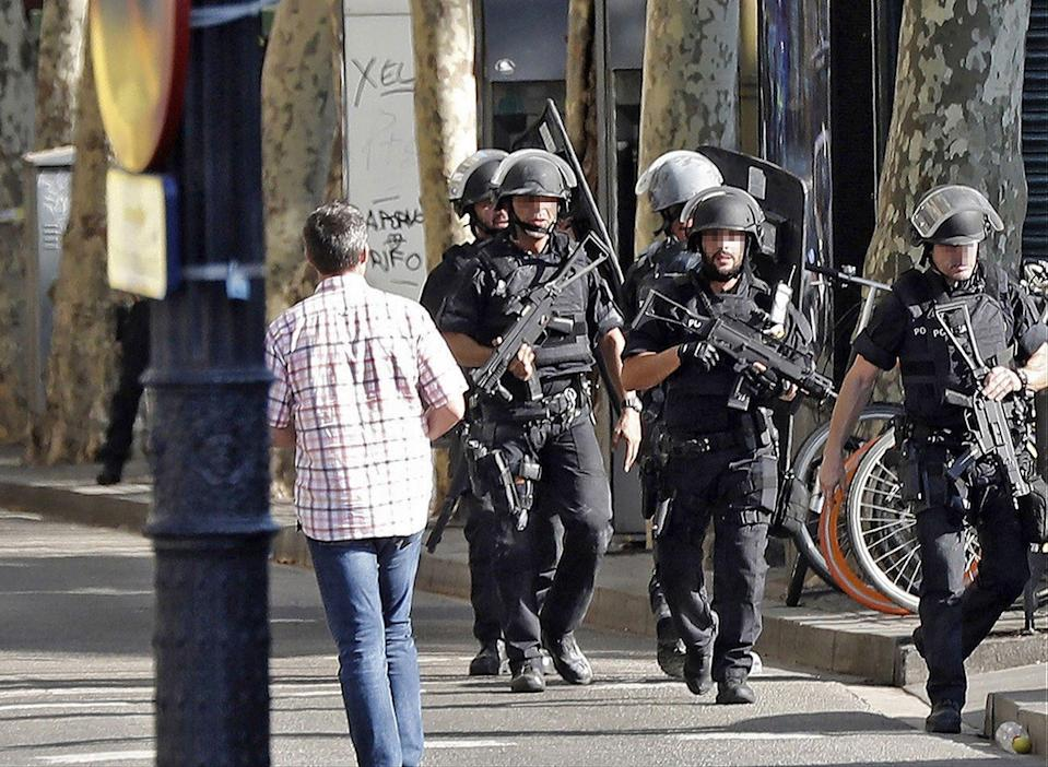 <p>Heavily armed police officers arrive for a manhunt near the site where a van crashes into pedestrians in Las Ramblas, downtown Barcelona, Spain, Aug. 17, 2017. (Andreu Dalmau/EPA/REX/Shutterstock) </p>