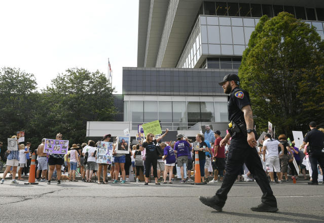 """FILE - In this Aug. 17, 2018 file photo, family and friends who have lost loved ones to OxyContin and opioid overdoses protest outside Purdue Pharma headquarters in Stamford, Conn. A member of the family that owns the company told people gathered at the prescription opioid painkiller OxyContin's launch party in the 1990s that it would be """"followed by a blizzard of prescriptions that will bury the competition."""" That's according to court documents filed Tuesday, Jan. 15, 2019, in a case brought by Massachusetts Attorney General Maura Healey that accuses the company and its executives of deceiving patients and doctors about the risks of opioids. (AP Photo/Jessica Hill, File)"""