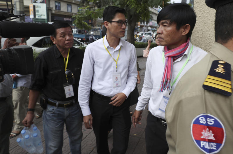 Journalists Uon Chhin, right, and Yeang Sothearin, center, prepare to enter the municipal court in Phnom Penh, Cambodia, Friday, Aug. 9, 2019. The two Cambodian journalists who had worked for U.S. government-funded Radio Free Asia were back on trial Friday on espionage charges that rights groups have characterized as a flagrant attack on press freedom. Uon Chhin and Yeang Sothearin are charged with undermining national security by supplying information to a foreign state, which is punishable by up to 15 years in prison. (AP Photo/Heng Sinith)
