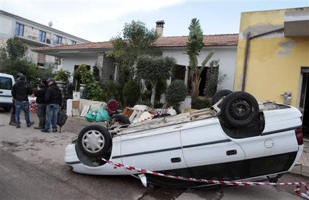 An overturned car is seen on a road following extreme rainfall in Olbia on Sardinia island November 20, 2013. REUTERS/Tony Gentile